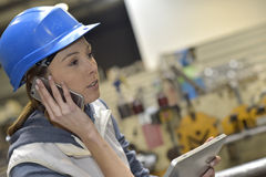 Woman in factory talking on a smartphone Stock Photos