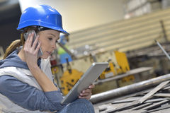 Woman in factory talking on a smartphone and using tablet Royalty Free Stock Photography