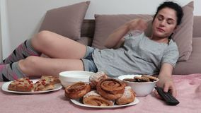 Woman fall asleep on bed after eating unhealthy food stock footage
