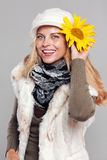 Woman in fall fashion holding a sunflower to her head and smiling Stock Images