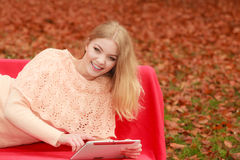 Woman in fall park with tablet browsing internet. Royalty Free Stock Images