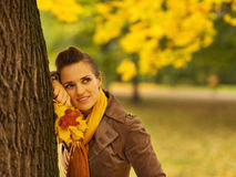 Woman with fallen leaves leaning against tree Royalty Free Stock Photo