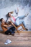Woman falling from chair. And men trying to catch her Royalty Free Stock Images