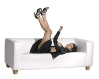 Woman falling on couch Stock Photo
