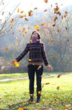 Woman and falling leaves. Woman throwing yellow leaves in the air Stock Photography