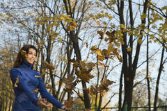 Woman With Falling Leaves In Park. Low angle view of a smiling woman with falling leaves in the park royalty free stock photography