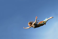 Woman Falling Through the Sky. A young woman is falling as if flying through the air in front of a blue sky background Royalty Free Stock Image