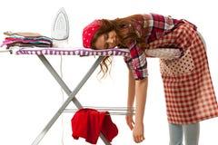 Woman falls asleep while ironing isolated over white background.  Stock Photo