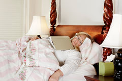 Woman falls asleep reading in bed Royalty Free Stock Image