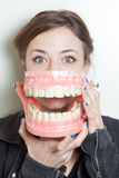 Woman false teeth. Pretty young woman with oversized false teeth denture royalty free stock photography