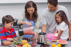 Woman with family pouring fruit from a blender Royalty Free Stock Photos