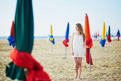Woman with famous colorful parasols on Deauville Beach in France Stock Photos