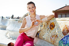 Woman on famous trencadis style showing heart shaped hands. Get inspired by Park Guell in your next trip to Barcelona, Spain. Happy young woman showing heart Stock Photos