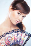 Woman with fan. Portrait of beautiful young woman with colorful tan Royalty Free Stock Images