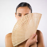Woman and fan. A studio portrait of a pretty young woman hiding her face with two fan Stock Images
