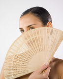 Woman and fan. A studio portrait of a pretty young woman hiding her face with a fan Royalty Free Stock Photography