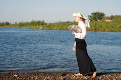 Woman with fan on the coast Stock Image