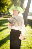 Woman with fan in the park Stock Image