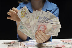 Woman With Fan Of Pound Currency Notes. Midsection of a woman with fan of pound currency notes against black background stock photos