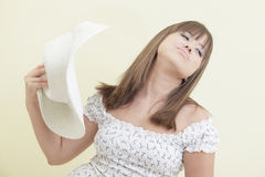 Woman fanning herself with a hat Royalty Free Stock Image