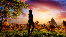 Woman On Fantasy Forest. Beautiful and elegant woman standing on a hill looking to the horizon in a fantasy forest environment with majestic clouds and a castle Royalty Free Stock Photography