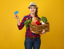 Woman farmer with box of fresh vegetables showing credit card Stock Images