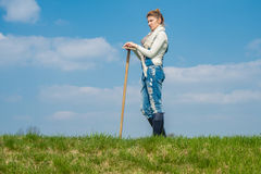 Woman farmer. A girl standing on the lawn with a hoe in his hand Stock Image