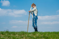 Woman farmer. A girl standing on the lawn with a hoe in his hand Royalty Free Stock Photo