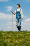 Woman farmer. A girl standing on the lawn with a hoe in his hand Royalty Free Stock Photos