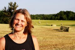 Woman farmer on a hay field. With bales in the background royalty free stock photo