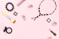 Woman fashion accessories, jewelry and cosmetics on pink background. Flat lay. Top view royalty free stock images