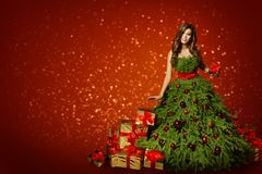 Woman in Fashion Christmas Tree Dress, Girl with Xmas Present. Gifts over New Year Red Background royalty free stock photos