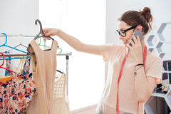 Woman Fashion Designer Choosing Dress And Talking On Mobile Phone Royalty Free Stock Image