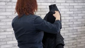 Woman fashion designer examines new clothes on mannequin looks at seams of vest. Tailoring in workshop. Sewing business. Woman fashion designer examines new stock video