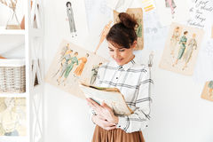 Woman fashion designer holding sketchbook while standing at her studio Royalty Free Stock Photo