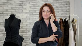 Woman fashion designer talks with client on smartphone in clothing atelier. Stylist is working in sewing factory workshop using mobile phone for job. Portrait stock footage