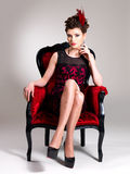Woman with fashion hairstyle and red armchair Royalty Free Stock Photography