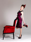 Woman with fashion hairstyle and red armchair Stock Photography
