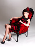 Woman with fashion hairstyle and red armchair Stock Images