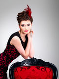 Woman with fashion hairstyle and red armchair Stock Photos