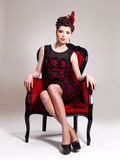 Woman with fashion hairstyle and red armchair Royalty Free Stock Photo