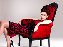 Woman with fashion hairstyle and red armchair Royalty Free Stock Photos