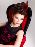 Woman with fashion hairstyle and red armchair Royalty Free Stock Image