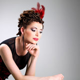 Woman with fashion hairstyle with red feather in hairs Royalty Free Stock Images