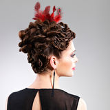Woman with fashion hairstyle with red feather in hairs Royalty Free Stock Photography