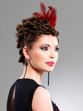Woman with fashion hairstyle with red feather in hairs Royalty Free Stock Photos