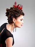 Woman with fashion hairstyle with red feather in hairs Stock Photography