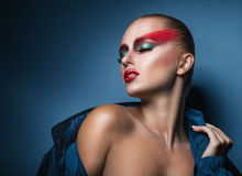 Woman with fashion make-up. Sexy woman with fashion make-up in the studio on a blue background Stock Photo