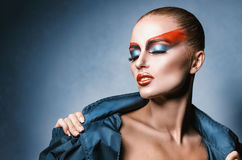 Woman with fashion make-up. Sexy woman with fashion make-up in the studio on a blue background Royalty Free Stock Image