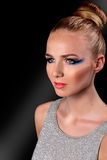 Woman in fashion makeup. Beautiful young blond woman in creative fashion makeup with a serious pensive expression staring straight ahead on a dark background Stock Photography